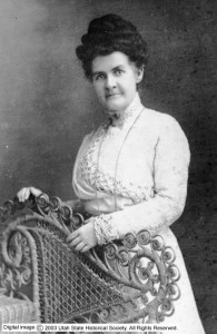 Martha Hughes Cannon stands wearing a high-necked white dress next to an elaborate wicker chair