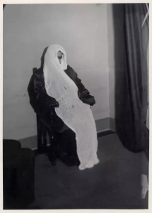 Helen Duncan sits on a chair with what appears to be a piece of long white fabric draped from her face over her head and dangling down to the floor at her feet.
