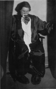 Helen Duncan sits on a chair wearing a blindfold. She has a piece of white something hanging out of her mouth with a woman's profile visible (apparently attached to the white material) in front of her neck.