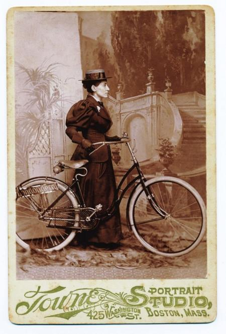 Annie Londonderry, wearing a black floor-length dress, hat, and gloves, stands in profile behind a bicycle.