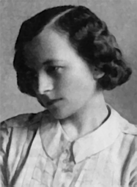 A young woman with dark hair and light skin looks down and to the left. She is wearing a blouse with a collar and what appears to be a floral pattern. Black and white photo.