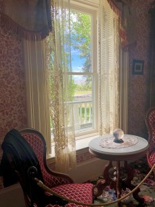 A large crystal ball sits on a small round table in front of a window with lace curtains. A red velvet armchair sits nearby.