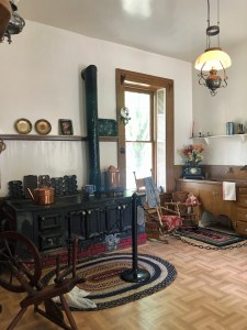 A 19th century kitchen with large wood stove, rag rugs, drying racks, plates on shelves, and other antique kitchenware.