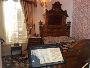 The room is dominated by a large intricately carved tall wooden headboard, the bed with a patchwork quilt, and the room with gold draperies, a beautiful floral-pattered rug, and other pieces of fine furniture.
