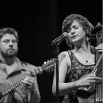 Image of the members of Half Pelican, holding instruments and playing in front of a mic on a stage - Eilley Bowers episode