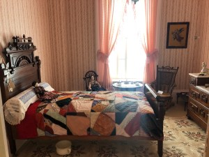 """A smaller but still very intricately patterned headboard on the bed, with a """"crazy-quilt"""" style cover in vibrant colors, pink draperies, striped vintage wallpaper, and a pair of rocking chairs with a doll sitting in one of them."""