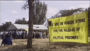 """A large sign reads """"We are on hunger strike for the release of the political prisoners"""" in front of a large crowd of people standing under a canopy."""