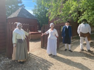 Costumed historical interpreters stand in front of a wooden gate welcoming visitors into the Randolph House museum. The people are wearing Colonial clothing - long full skirts and mob caps on the women, short trousers, oversized shirts and tricorn hats on the men.