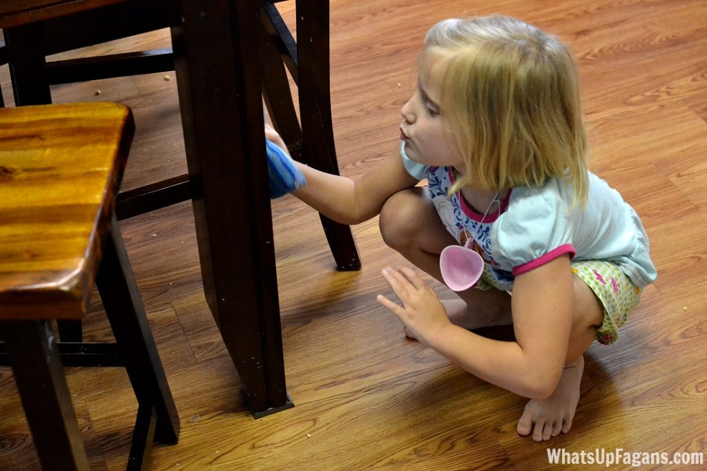 A little girl wipes down a table leg