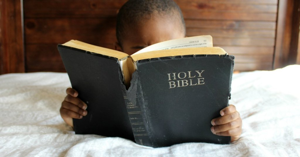 young black boy reading a worn Holy Bible on a bed as he tries to memorize scripture