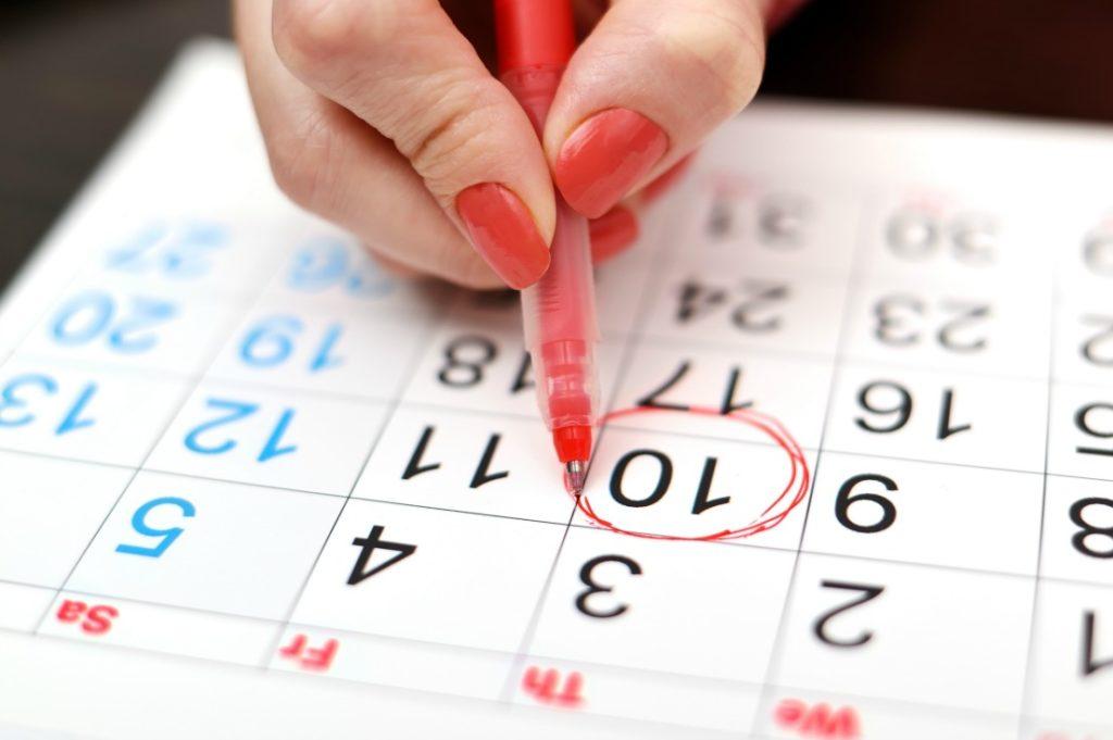close-up of woman highlighting date on calendar