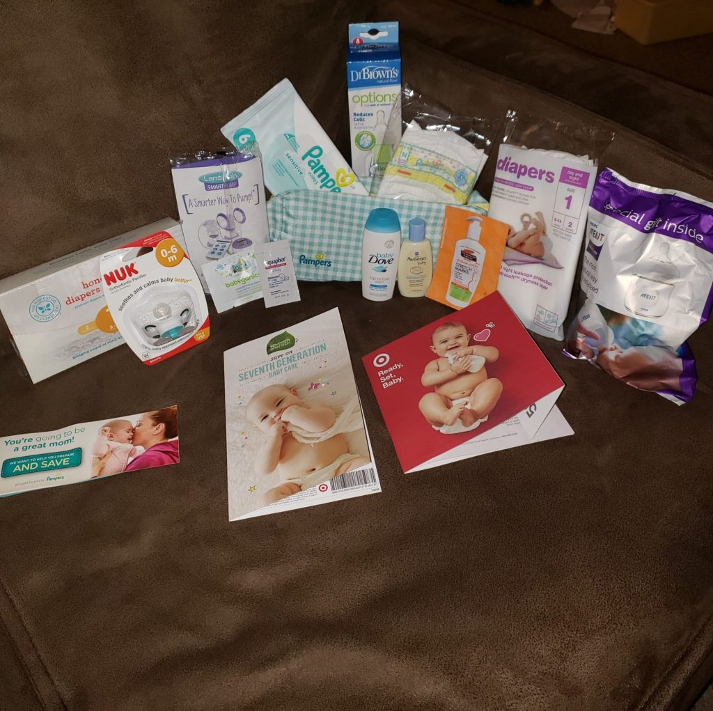 picture of target baby registry free gift inserts, coupons, and baby items laid out on a couch