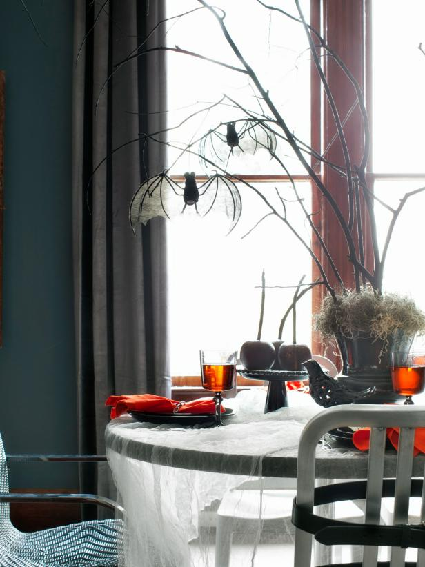 This dead-branch centerpiece with hanging bats is super cool and easy Halloween table decorations idea!