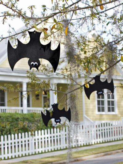 foam bats with googly eyes hanging upside down from tree outside as easy Halloween yard decorations to make