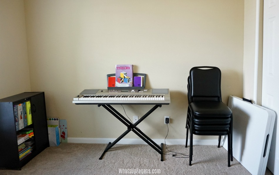 homeschooling in a small house - homeschooling room with piano, folding table, and stackable padded chairs and cabinet