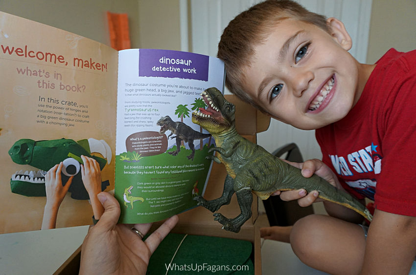 young boy holding dinosaur toy next to Kiwi Crate's felt dinosaur head costume instruction booklet