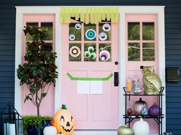 cheap and easy Halloween door decorations from HGTV where you make your front door covered with eyeballs and a simple mouth using just paper, tape, and streamers