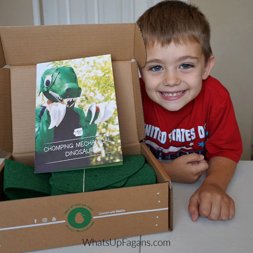 little boy smiling and posing with Kiwi Crate box featuring a chomping mechanical dinosaur kit that helps you make a 3d dinosaur head
