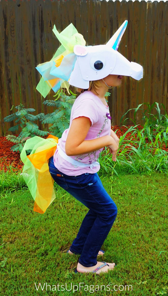 little girl sporting a DIY unicorn head piece in prancing position.