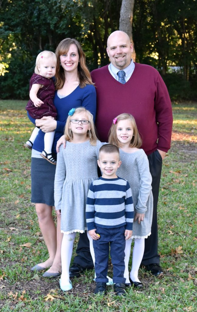 Mom and Dad and four young kids standing for family pictures. They have tips for preparing for family photo session as they took this photo themselves.