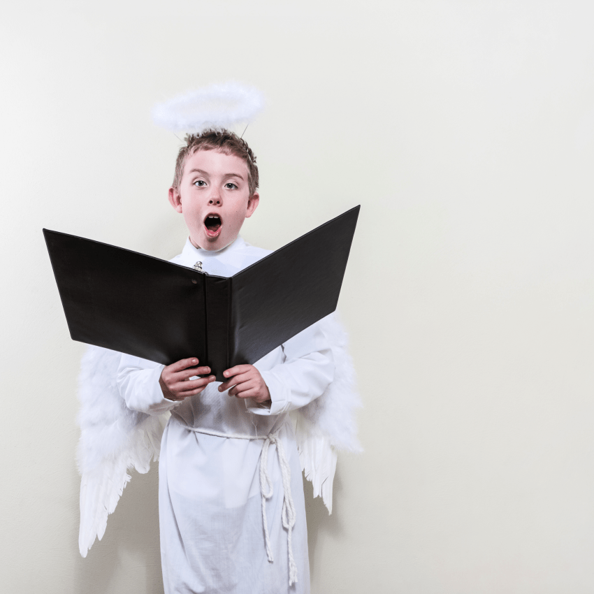boy dressed like an angel singing christian christmas music during the holidays