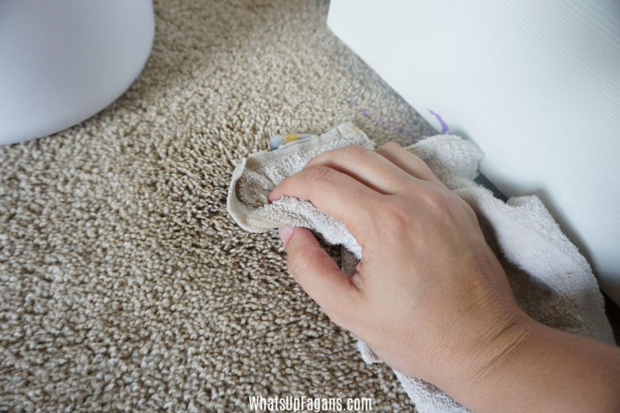 hand scrubbing the floor with soapy water rag, removing acrylic paint from carpet