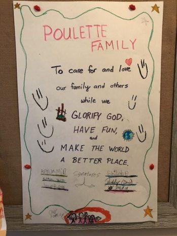 Poulette family mission statement example written on posterboard and hung on wall and signed by all the family members