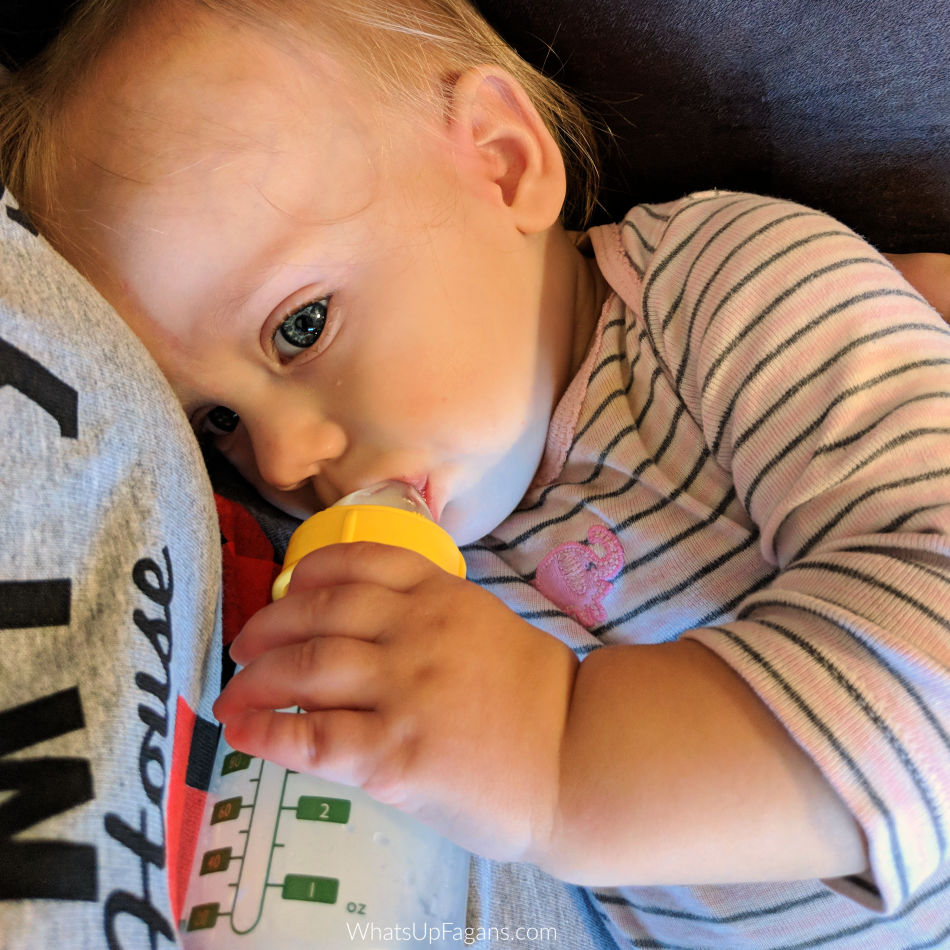 Baby drinking best breastfeeding supplement formula from her mother who is learning how to supplement with formula while breastfeeding