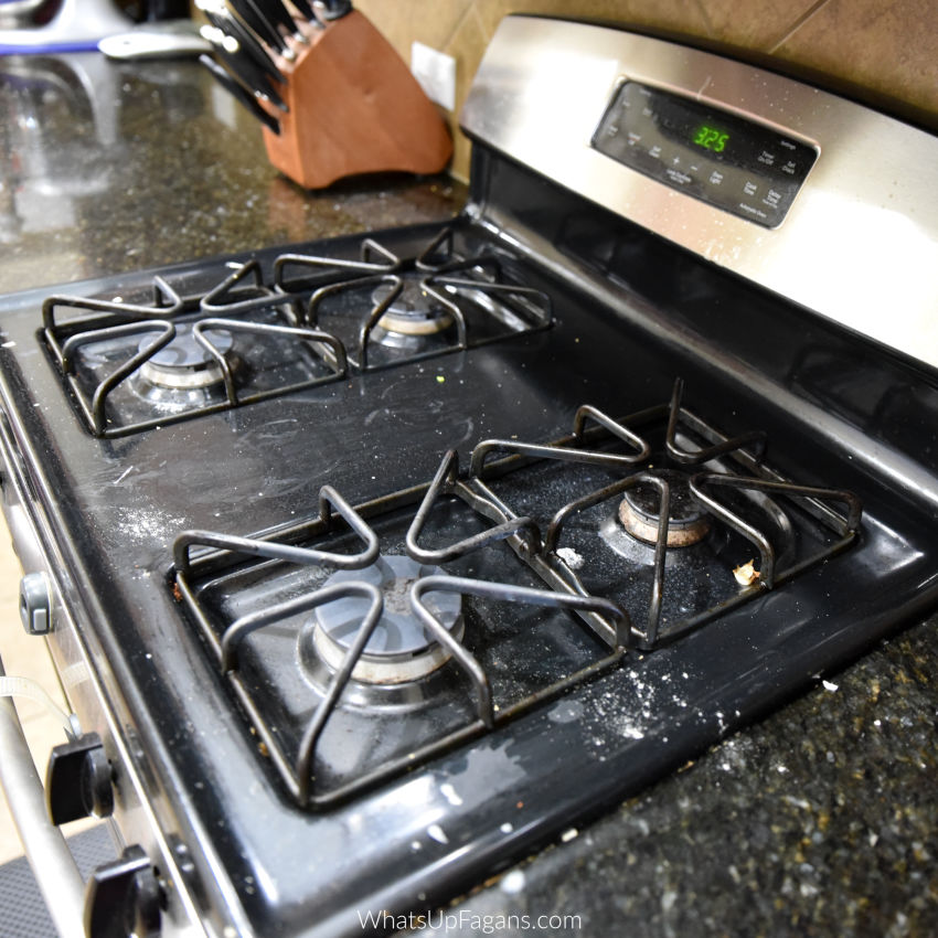best way to clean top of gas stove because this is an image of a dirty gas stove top