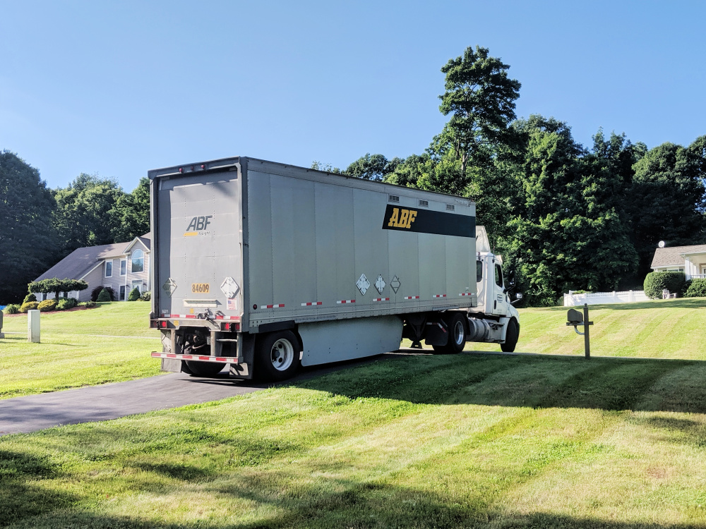 ABF UPack moving trailer backing into residential driveway