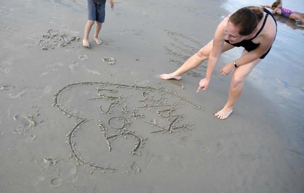 women writing Josh + Kate in a heart on the sand as part of a beach themed game