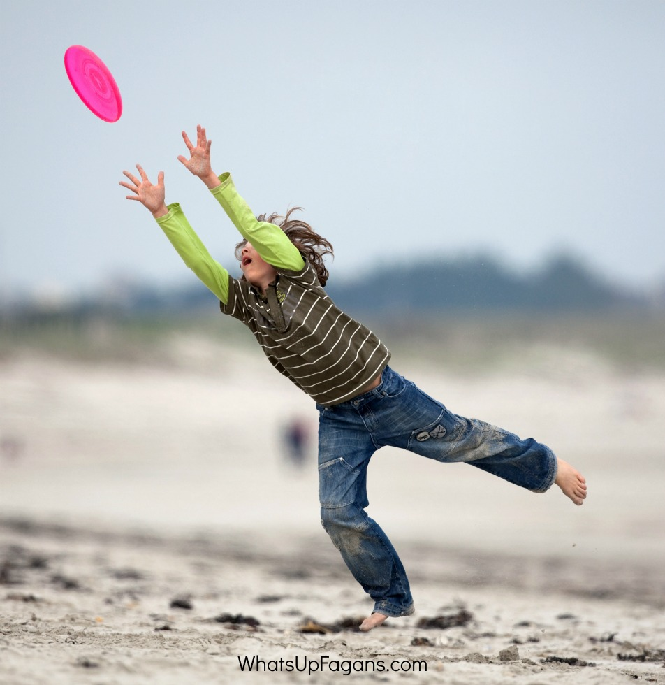 games to play at the beach include multiple different Frisbee games. Here is a boy leaping in the air at the beach to catch a pink Frisbee