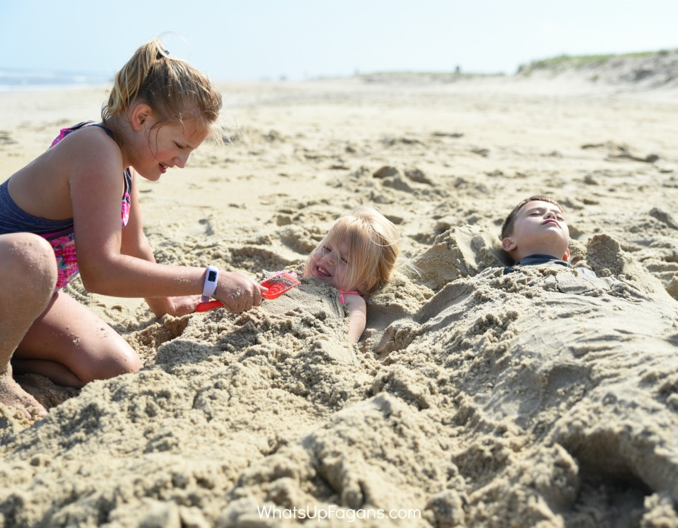 Girl burying two younger siblings in the sand as part of a fun beach game for kids