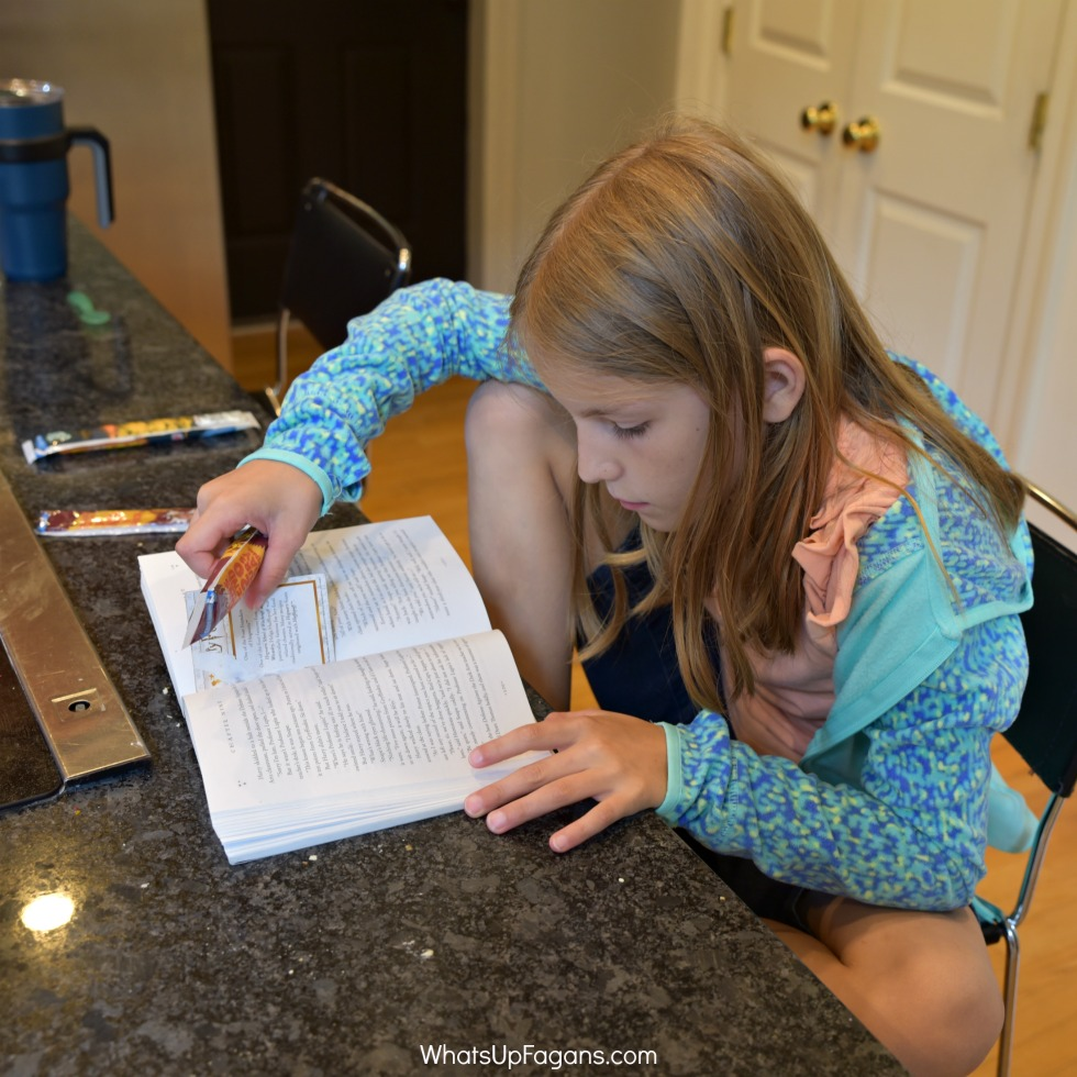 girl reading book while eating yoplait Go Gurt as part of a homeschool routine