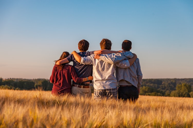 four teenage friends standing in a field looking away into the distance, with arms around each other, showing that kids will feel more secure when there is parental involvement in the home.