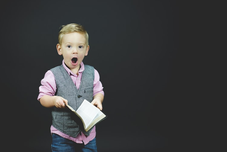 Child, boy, with surprised face, with open book in his hands, surprised by important role of parent involvement