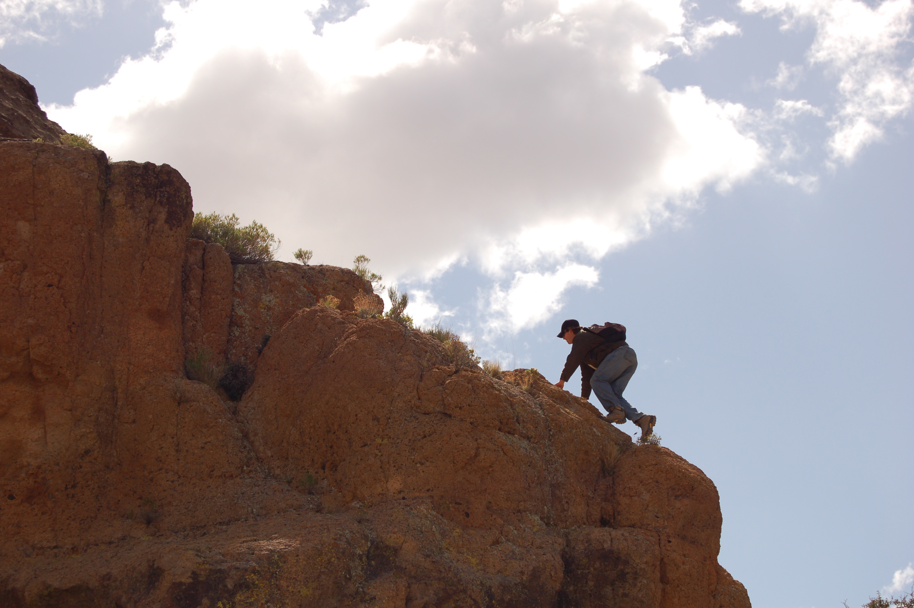A man climbs on a cliff edge looking for rock samples