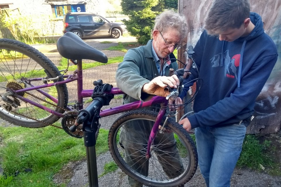 Ian teaching bike maintenance at Wheatland Farm's Devon eco lodges