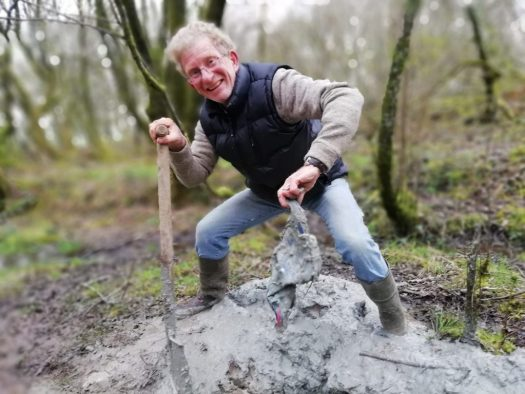 Ian digs a welly out of the mud at Wheatland Farm's Devon eco lodges.