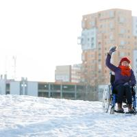 waving happy young adult woman on wheelchair in the city in winter at sunset