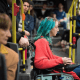 A young woman with blue hair (Juana) in a power wheelchair on a public bus
