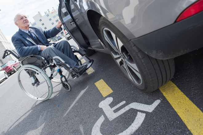 senior wheelchair user getting into his car