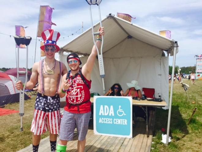 Two men standing, one with a cast on his leg holding up a crutch in front of the ADA Access Center tent at a festival