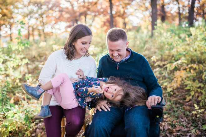 Melissa Ingram sitting on a stool next to her husband, Kirk Ingram, who is sitting in his wheelchair. Their 4-year-old daughter is lying across their laps.