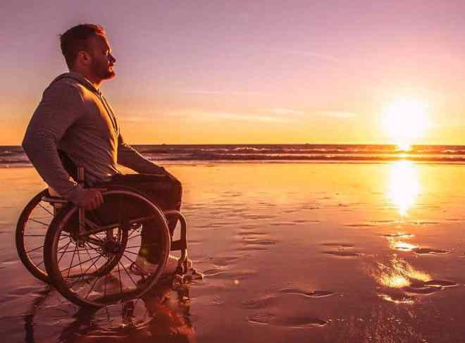 Richard Corbett is sitting in his chair on the shore of a beach. The sun is setting in the horizon.