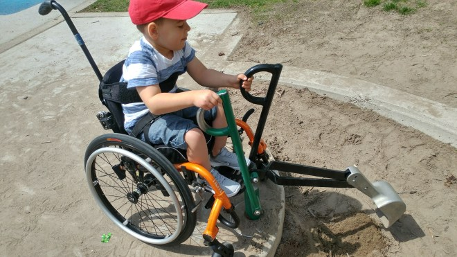 a little boy with a red baseball cap is sitting in his orange wheelchair and using an adaptive tool to dig in the sand