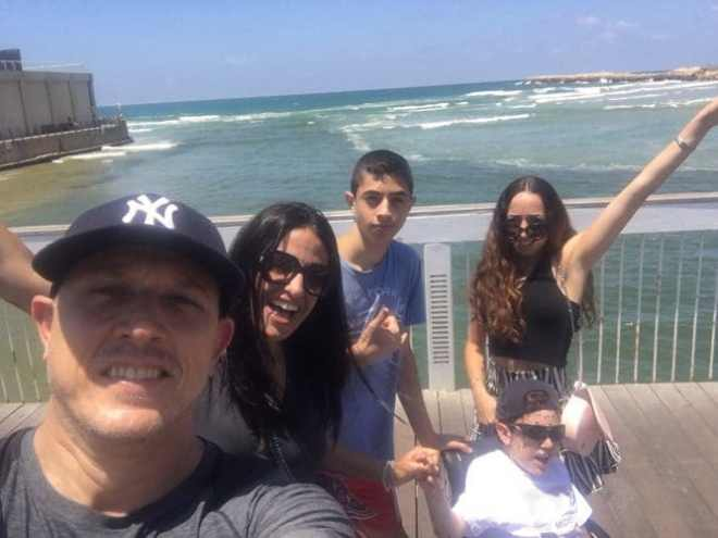 Erez with his family on a boardwalk overlooking the sea