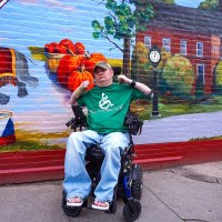 Tim Taylor sits in his power wheelchair in front of a colorful mural.