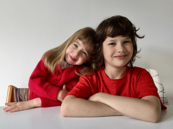 Eudora, a little girl with dirty blond hair wearing a read sweater, rests her head on her brother's shoulder, a boy with wispy dark brown hair wearing a read t-shirt.