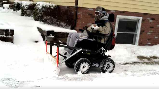 Tim Taylor plows snow with his 4x4 wheelchair and plow attachment he designed.
